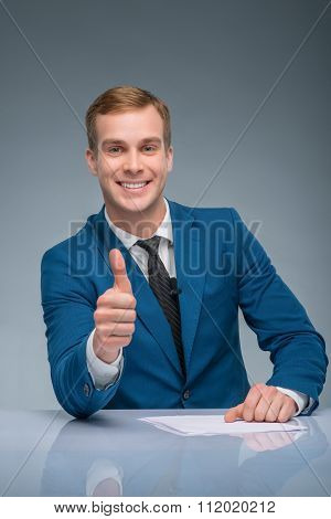 Smiling newscaster showing thumbs up.