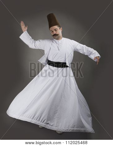 Mevlana dervish whirling over gray background.