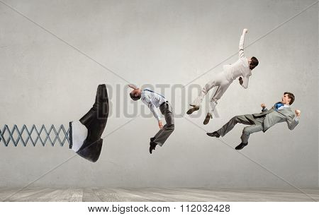 Big businessman foot on spring kicking business people