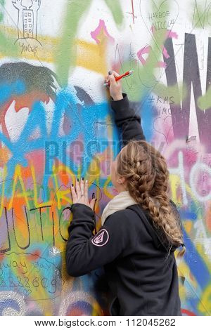 Woman Writes On Colorful Painted Wall
