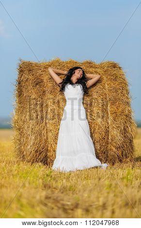 Beautiful brunette woman near hay bale in warm summer day