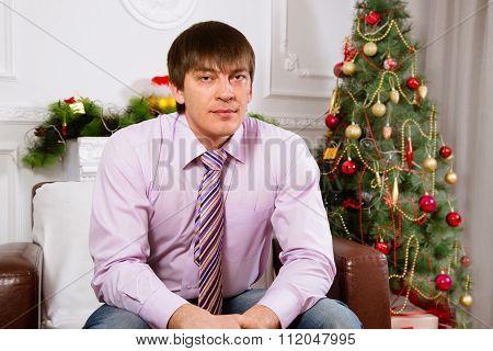 Portrait of the serious man near a Christmas fir-tree.