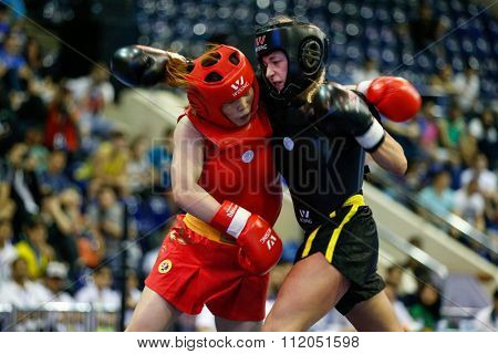 JAKARTA, INDONESIA - NOVEMBER 18, 2015: Ling Ling Liu of China (red) fights Elin Oberg of Sweden (black) in the women's 56kg Sanda event finals at the 13th World Wushu Championship 2015 in Jakarta.