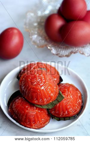 Ang ku kueh or chinese red tortoise cake is traditionally eaten together with dyed red eggs and mandarin oranges to celebrate the first month of a baby's birth