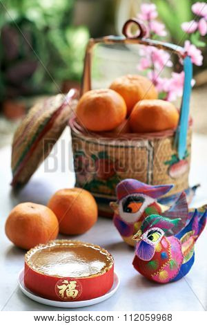 Traditional gift of glutinous rice cake and basket of mandarin oranges in celebration of chinese new year spring festival displayed with decorative ducks
