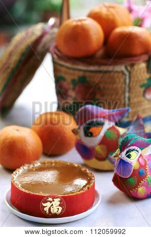 Traditional gift of glutinous rice cake and basket of mandarin oranges in celebration of chinese lunar new year spring festival displayed with decorative ducks