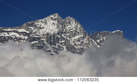 High Mountain In The Himalayas Reaching Out Of Clouds