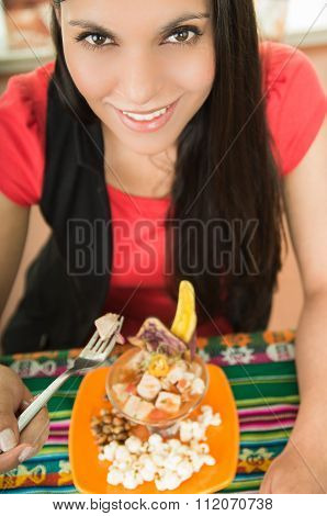 Beautiful young girl tasting a delicious fish ceviche, typical ecuadorian plate