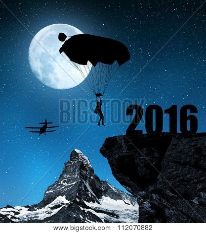 Silhouette skydiver parachutist landing in to the New Year 2016 in night.