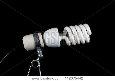 A clamp light with CFL bulb on a black background. poster