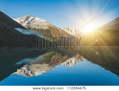 Sunrise And Mountains Reflected In The Water