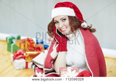 Pretty And Laughing Red-haired Cucasian Santa Girl With A Bunch Of Gift Boxes Speaking By Cellphone