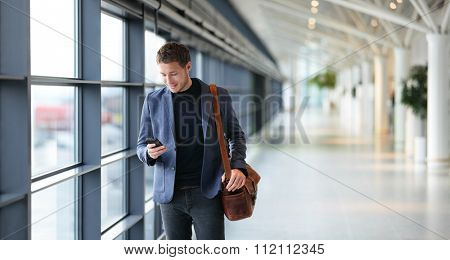 Man on smart phone - young businessman in airport. Casual urban professional business man using smartphone smiling happy inside office building. Handsome man wearing suit jacket indoors.