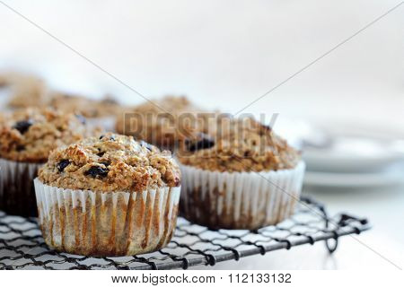 Healthy wholewheat bran muffins on cooling tray, a nutritious and fiber rich breakfast with cutlery and copyspace in the background