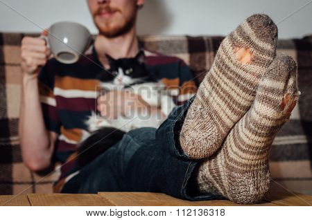 Young Man Sitting On Couch With Cat In Holey Socks