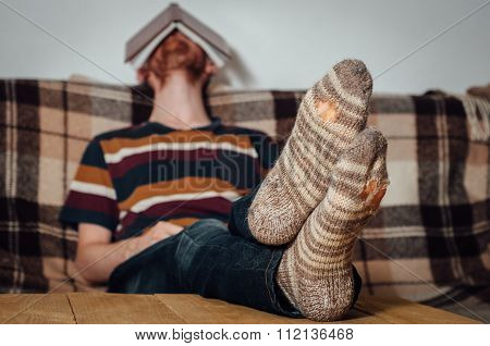Young Man Sleeping With Book On Couch In Holey Socks