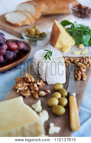Cheese platter starter appetiser pre-dinner snack, assortment of different cheeses, nuts, olives and grapes