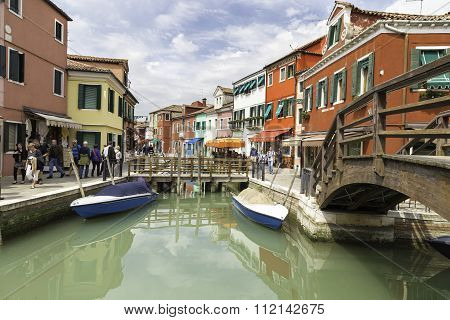Tourists Walking In Burano City Streets And Boats In The Lagoon In Beautiful City Of Burano