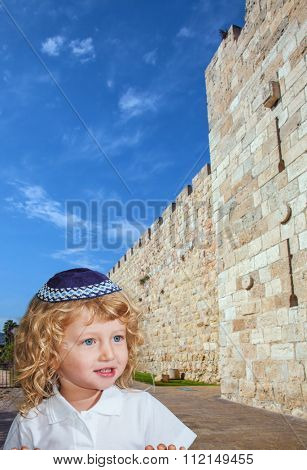 The Jewish holiday of Sukkot. Cute little boy with long blond curls and blue eyes in a knitted skullcap. He stands at the fortress walls of the Old City of Jerusalem