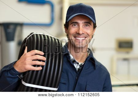 Portrait of a smiling worker carrying corrugated conduit
