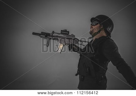 airsoft player with gun, helmet and bulletproof vest on gray background