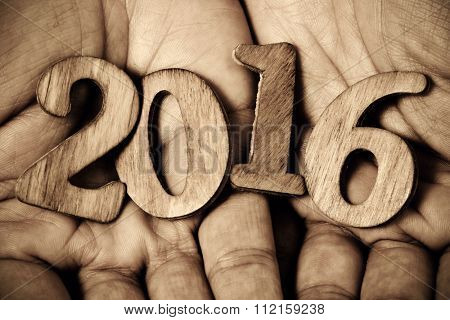 closeup of wooden numbers forming the number 2016, as the new year, in the hands of a man