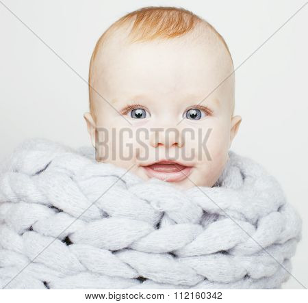 little cute red head baby in scarf all over him close up isolated, adorable kid winter clothers