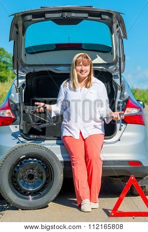 50 Years Old Smiling Woman Near The Car With A Punctured Tire