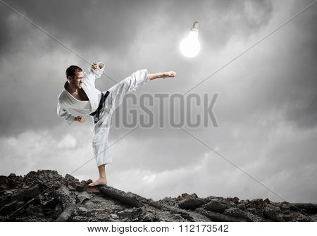 Young determined karate man breaking with leg light bulb