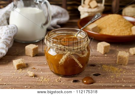 Homemade Caramel Sauce On Wooden Table
