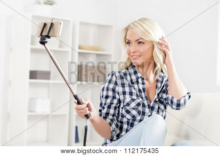Beautiful woman taking selfie with a stick on a sofa.