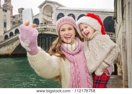 Happy Mother And Child In Santa Hat Taking Selfie In Venice