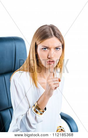 Portrait of young businesswoman in bossy chair. Businesswoman on white background seriously looking at camera and making silence gesture