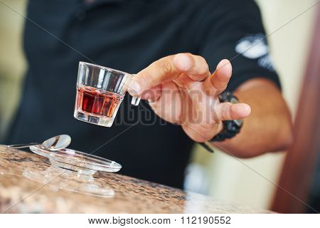 sommelier barman hand holding a little wine glass with alcohol aperitif liquor