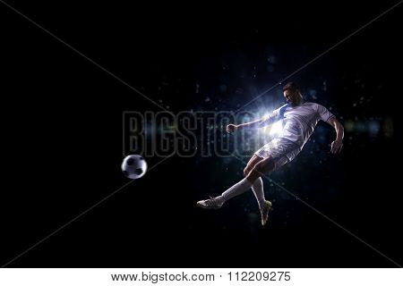 Soccer player in action over black background