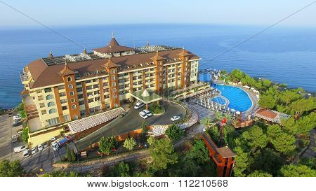ALANIA - AUG 16, 2015: Hotel Utopia World on top of hill near sea at summer sunny day. Aerial view videoframe. Hotel Utopia World is a 5-star resort with total area of about 100000sq.m.
