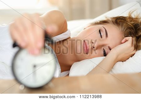 Sleepy Young Woman Portrait With One Opened Eye Trying Kill Alarm Clock