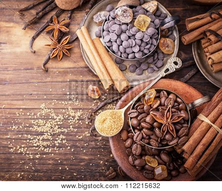 Coffee beans, chocolate drops, vanilla pods, cinnamon sticks, anise stars and brown sugar in a vintage silver cups on a dark textural wooden background. selective Focus poster