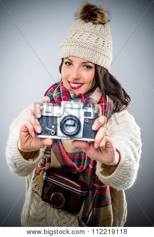 Smiling female photographer with a vintage camera