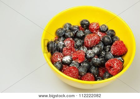 Frosted Raspberries And Blueberries In A Bowl, Isolated On White Background.