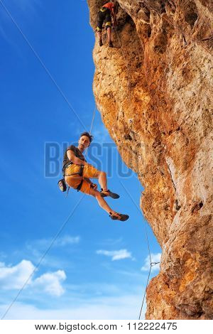 Rock Climber Hanging On Belay Rope Againstthe Mountains