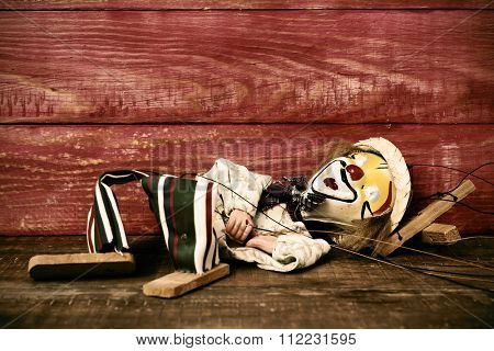an old marionette with its face painted like a clown dropped on a rustic wooden surface, with a filter effect