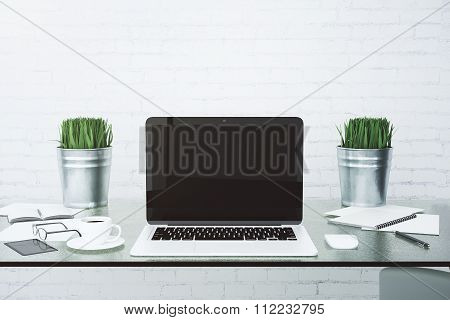 Blank Black Laptop Screen With Accesories And Grass In Buckets On Glassy Table At White Brick Wall B