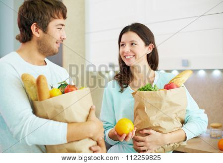 Young couple holding paper packets with products