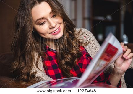 Portrait of a smiling woman reading magazine at home