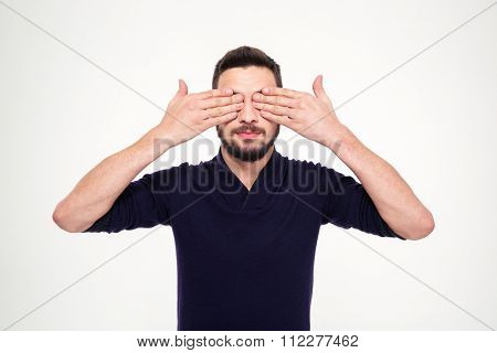 Handsome young bearded man in sweetshirt closed eyes with hands over white background