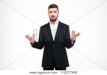 Handsome puzzled young businessman with beard in black suit and white shirt holding copyspace in both hands over white background