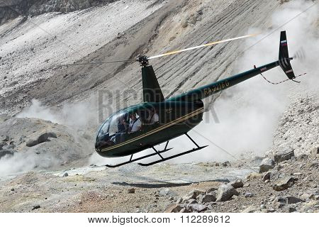 Touristic Helicopter Takes Off In Crater Of Active Volcano On Background Of Steaming Fumaroles