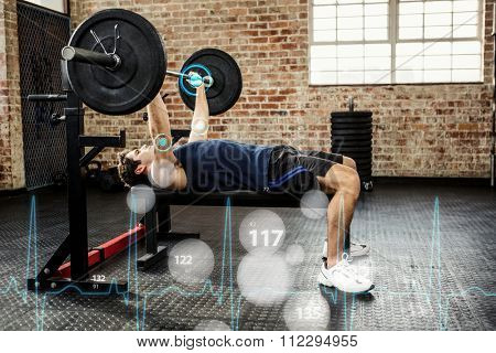 Side view of a man lifting barbell against heart rate monitor
