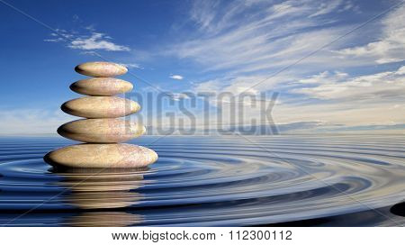 Zen stones stack from large to small  in water with circular waves and peaceful sky.